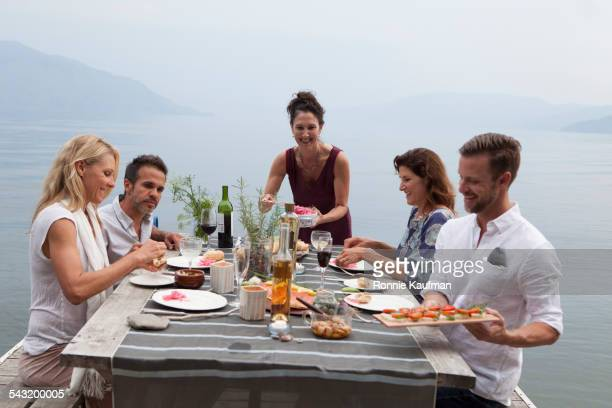 Caucasian friends eating lunch near lake
