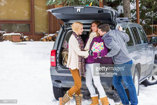 Caucasian friends laughing with gifts at car in winter