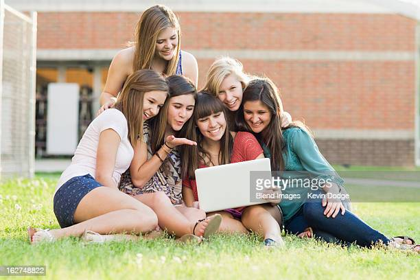 Caucasian friends looking at laptop together