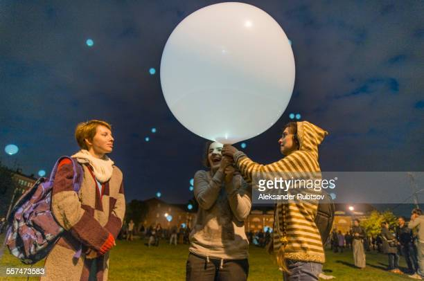 Caucasian friends playing with balloon in park