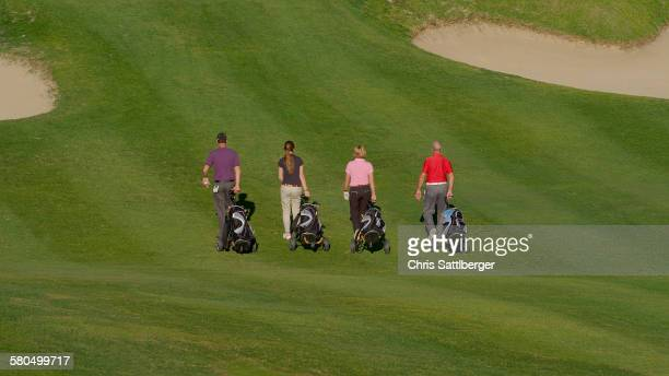 Caucasian friends pulling golf bags on course