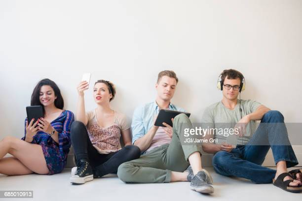 Caucasian friends sitting on floor using technology