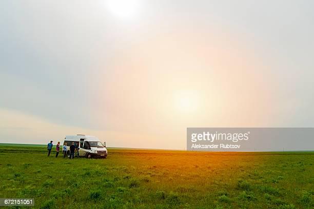 Caucasian friends standing in field near van