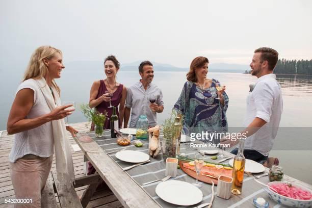 Caucasian friends talking at picnic table at lake