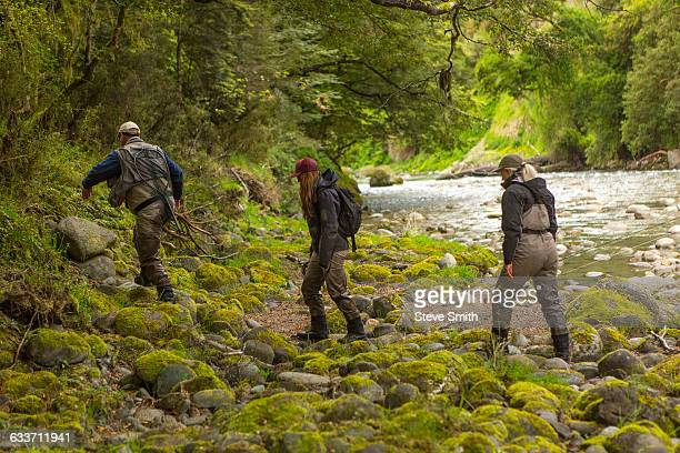 caucasian friends walking in remote river - nelson city new zealand stock pictures, royalty-free photos & images