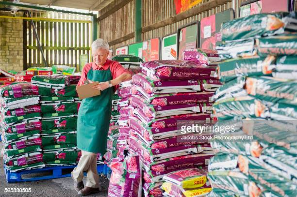 caucasian gardener checking inventory in nursery - abundance stock pictures, royalty-free photos & images