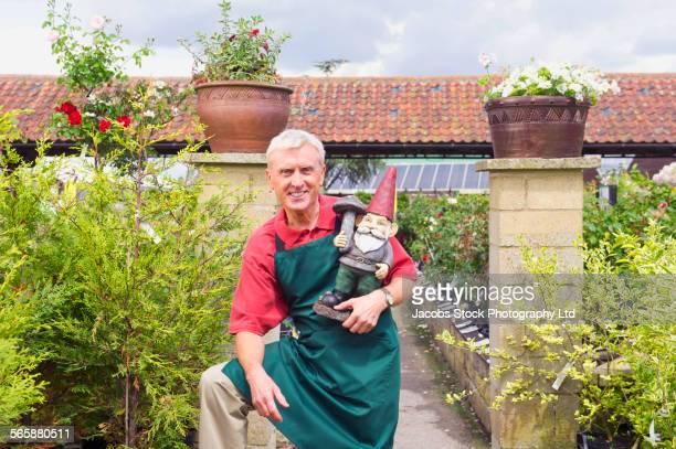 Caucasian gardener holding garden gnome in nursery