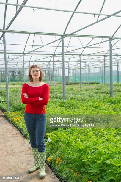 Caucasian gardener smiling near plants in greenhouse