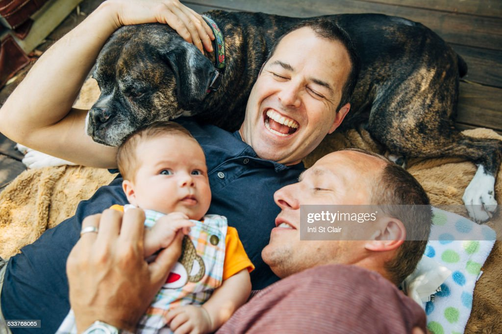 Caucasian gay couple cuddling baby boy and dog : Stock Photo
