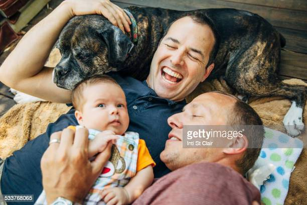 Caucasian gay couple cuddling baby boy and dog