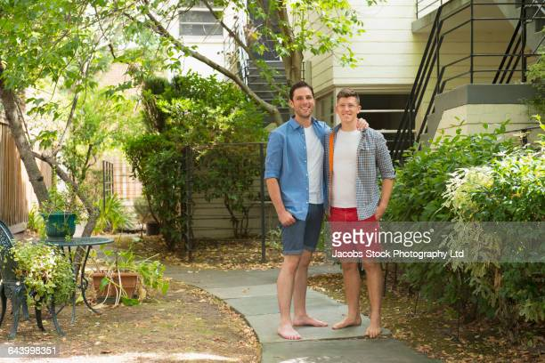 Caucasian gay couple smiling in garden