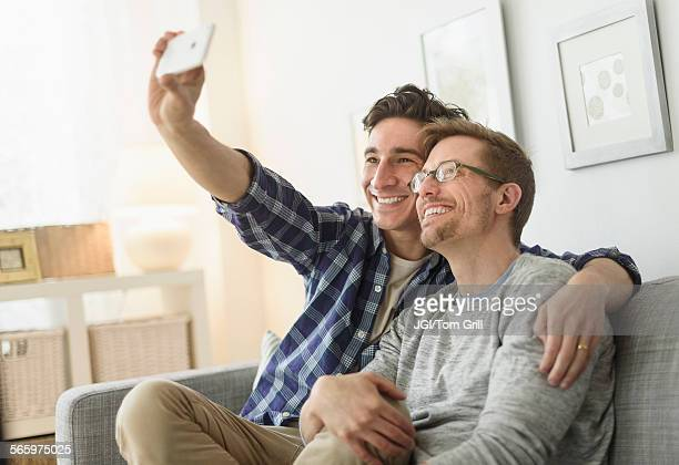 Caucasian gay couple taking selfie on sofa