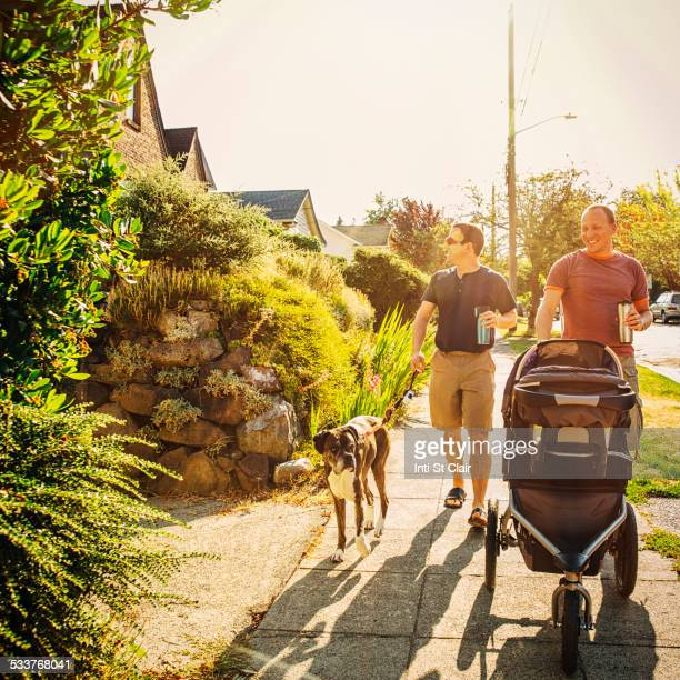 Caucasian gay couple walking dog and pushing stroller on sidewalk