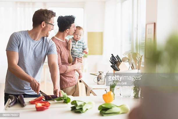 caucasian gay fathers and baby cooking in kitchen - union gay fotografías e imágenes de stock