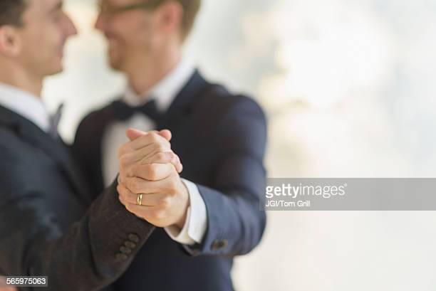 Caucasian gay grooms dancing at wedding