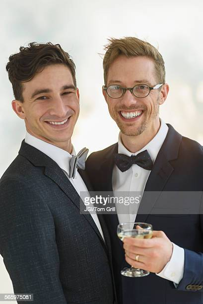 Caucasian gay grooms drinking champagne at wedding