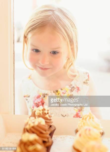 Caucasian girl admiring cupcakes in bakery window