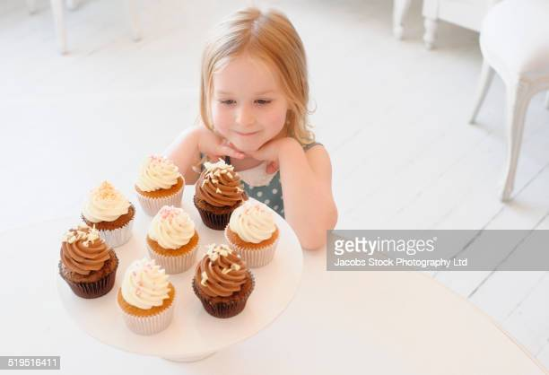 Caucasian girl admiring tray of cupcakes