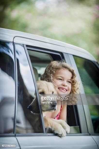 Caucasian girl and dog leaning on car window