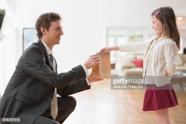 Caucasian girl and father holding bag lunch