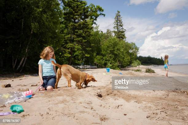 Caucasian girl and puppy playing on beach
