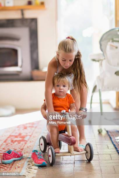 Caucasian girl and toddler brother playing in living room