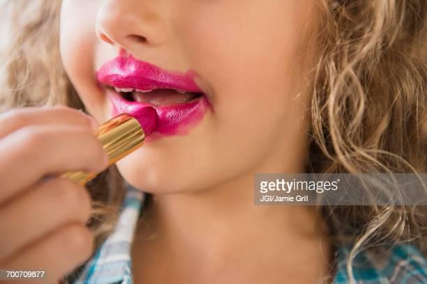 Caucasian girl applying messy lipstick