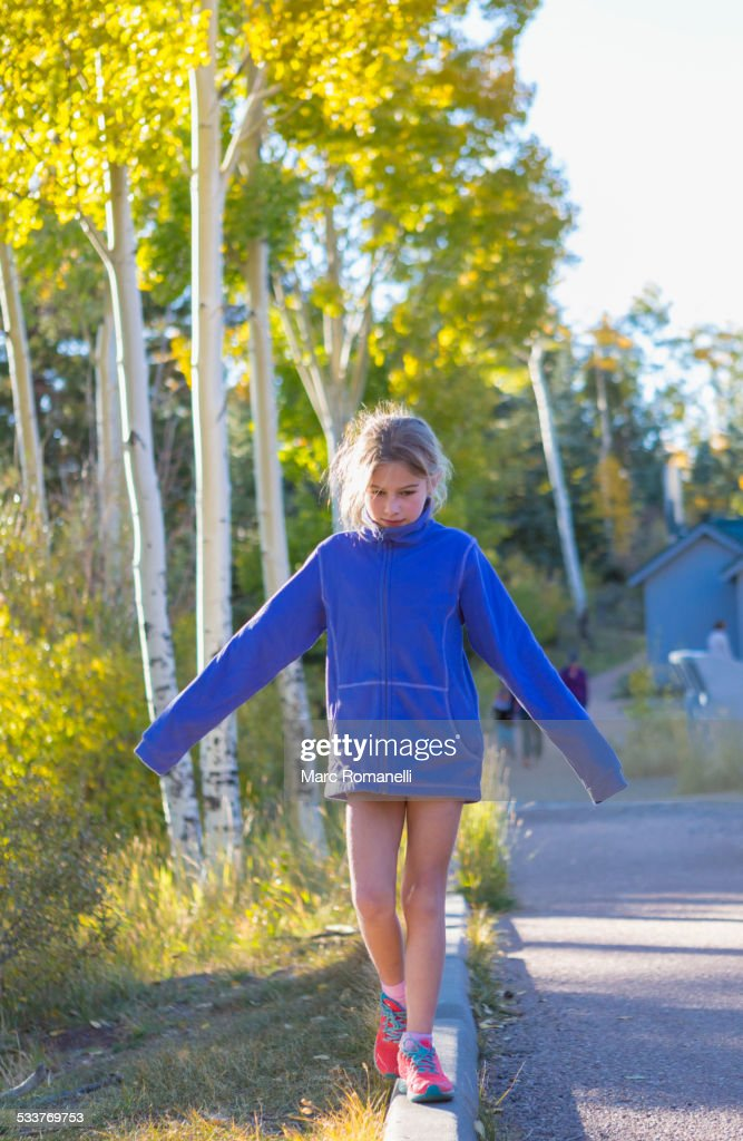 Caucasian girl balancing on concrete curb : Foto stock