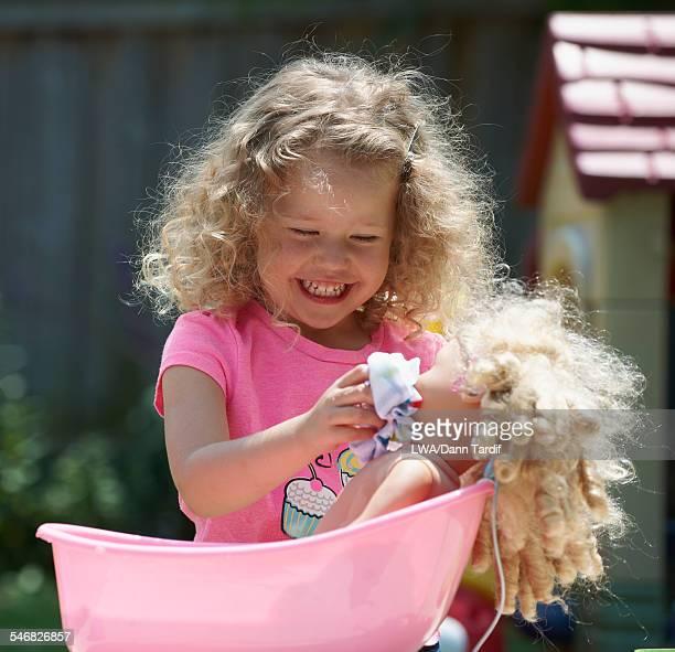 Caucasian girl bathing doll outdoors