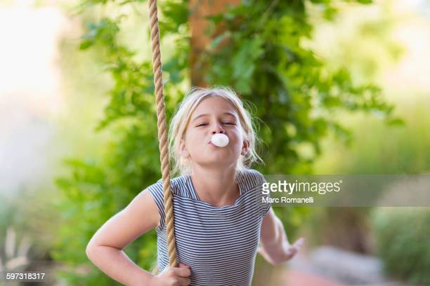 Caucasian girl blowing bubble gum bubble