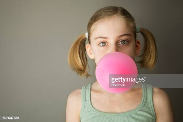 Caucasian girl blowing gum bubble