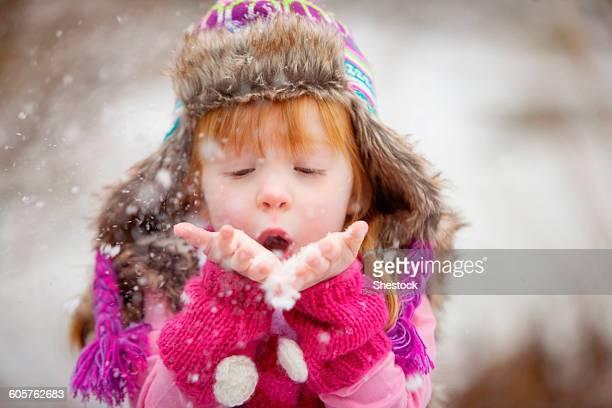 Caucasian girl blowing handful of snow