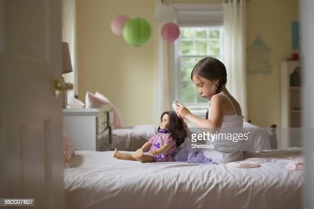 Caucasian girl brushing hair of doll on bed
