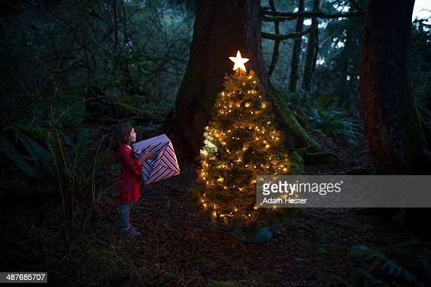Caucasian girl by Christmas tree in forest