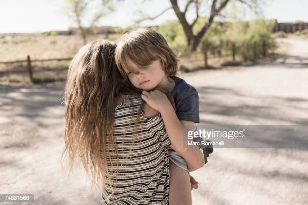 Caucasian girl carrying brother on dirt path