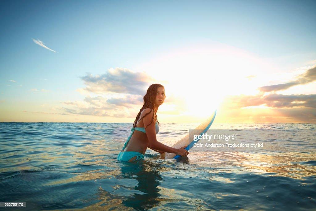 Caucasian girl carrying surfboard in ocean : Foto stock