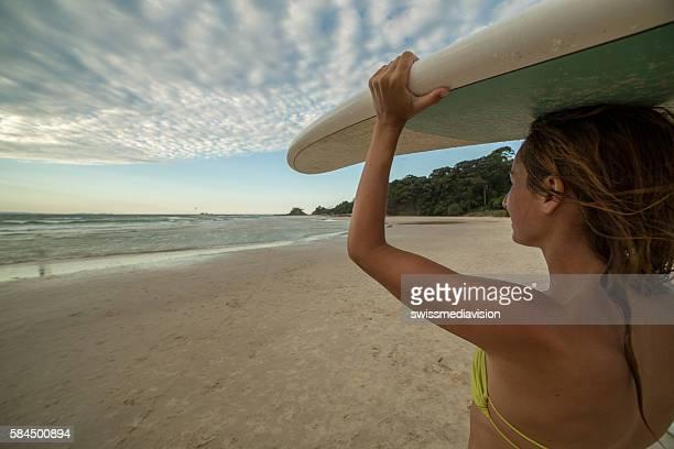 Caucasian girl carrying surfboard on beach