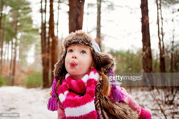 Caucasian girl catching snow on tongue