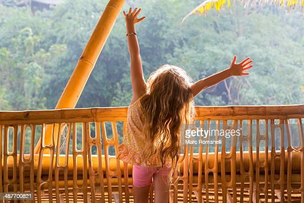 Caucasian girl cheering on bamboo balcony