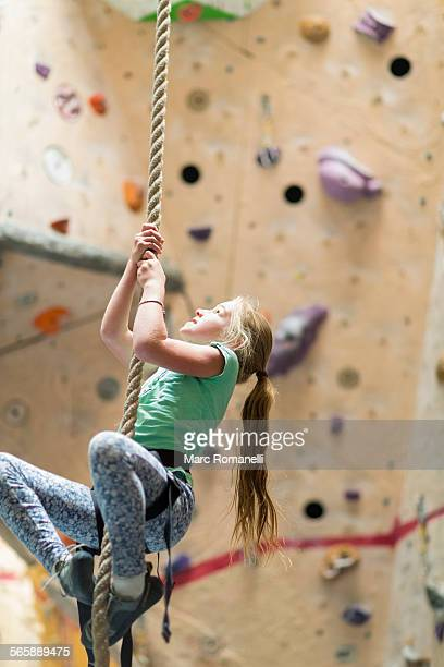 Caucasian girl climbing rope on rock wall indoors