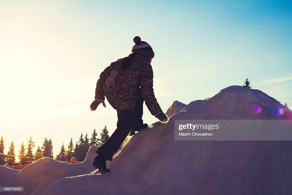 Caucasian girl climbing snowy hill : Foto stock