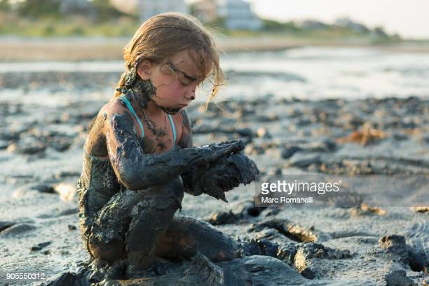 caucasian girl covered in mud playing on beach - saint simon's island stock pictures, royalty-free photos & images