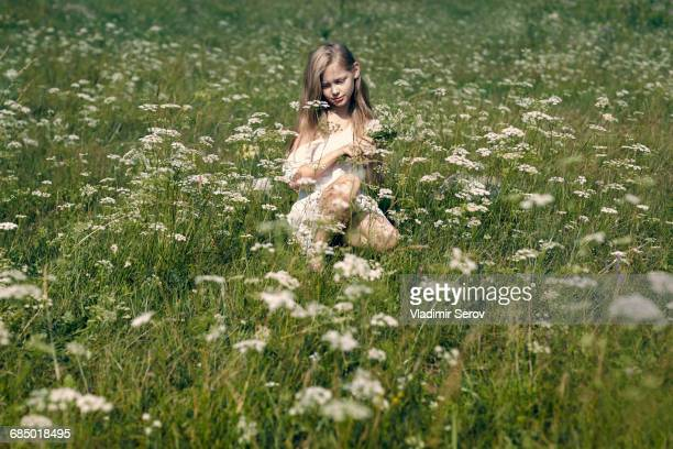 Caucasian girl crouching in field picking wildflowers