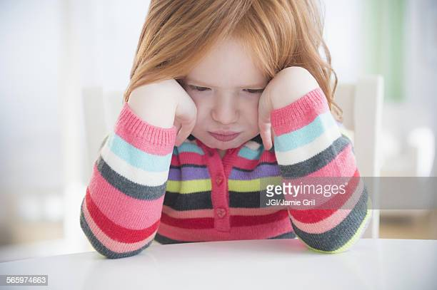 Caucasian girl crying at table
