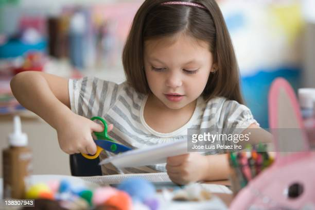 caucasian girl cutting paper with scissors - arti e mestieri foto e immagini stock