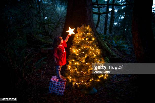 Caucasian girl decorating Christmas tree in forest