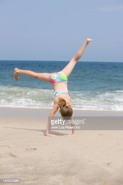 caucasian girl doing cartwheel on beach - girl with legs spread stock photos and pictures