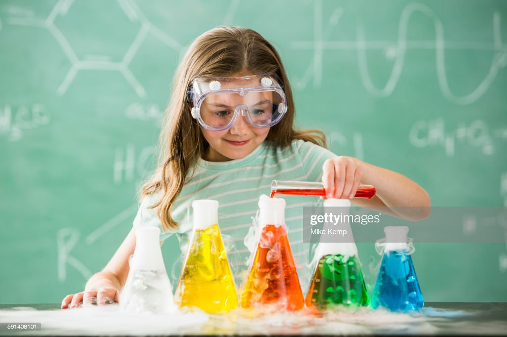 Caucasian girl doing science experiment in classroom : Stock Photo
