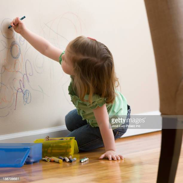 Caucasian girl drawing on wall