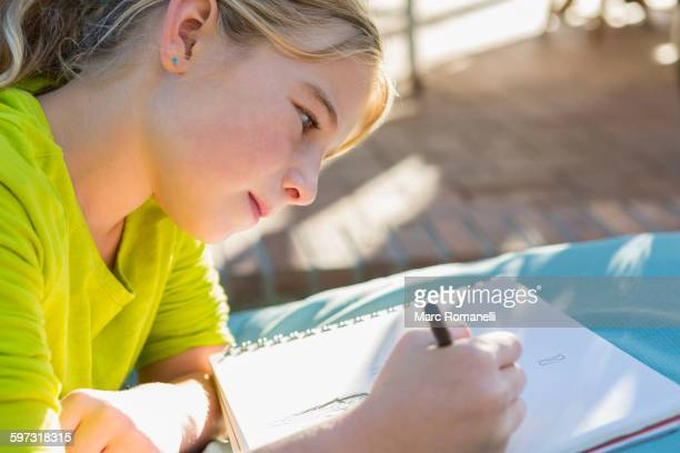 Caucasian girl drawing outdoors